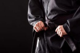 Closeup of male karate fighter tying the knot to his black belt